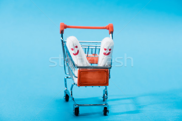 two menstrual tampons with happy smileys in small shopping cart on blue Stock photo © LightFieldStudios