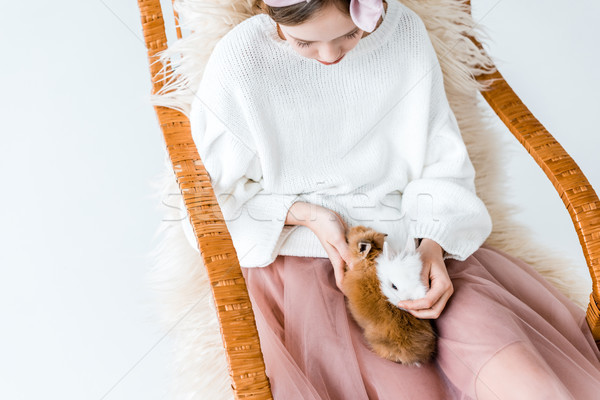 high angle view of girl with cute furry bunnies sitting in rocking chair Stock photo © LightFieldStudios