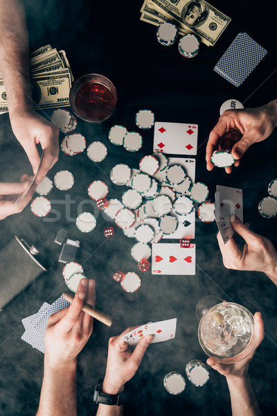 Smoke over people playing poker by casino table with cards and chips Stock photo © LightFieldStudios