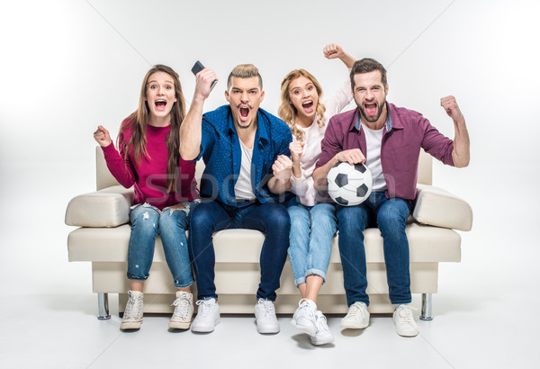 Friends sitting on couch with soccer ball   Stock photo © LightFieldStudios