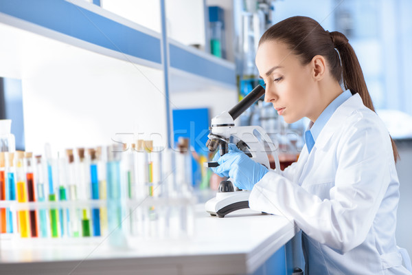 side view of concentrated scientist working with microscope Stock photo © LightFieldStudios