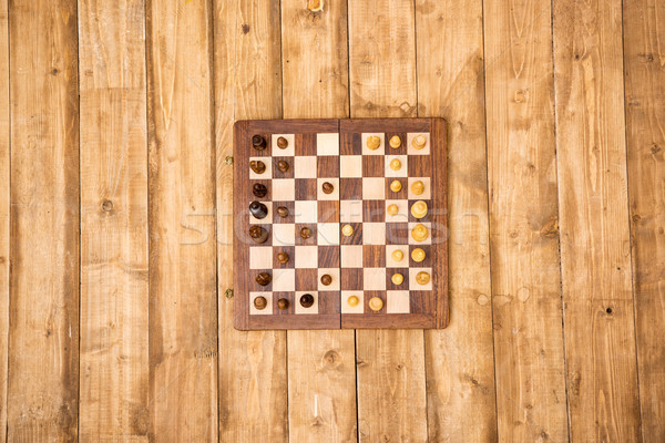 Top view of wooden chessboard with pieces on brown wooden planks Stock photo © LightFieldStudios