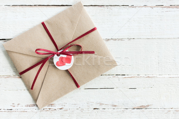 Stock photo: Top view of decorative kraft envelope with tag and ribbon on wooden tabletop, wedding invitation car