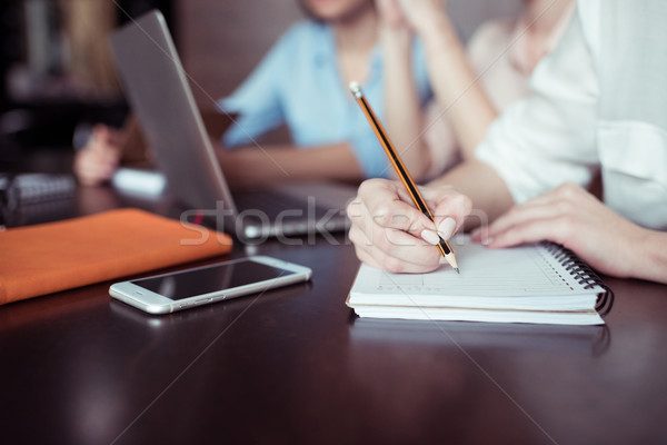 partial view of businesswoman writing notes with coworkers working near by Stock photo © LightFieldStudios