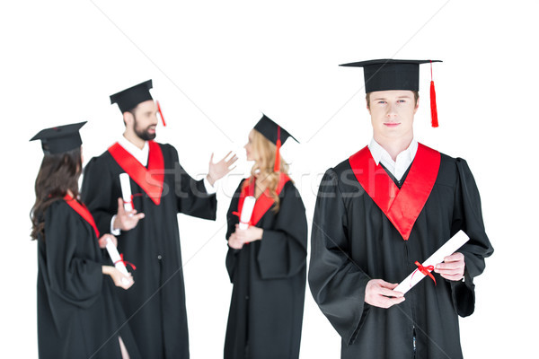 Young student in graduation cap with diploma and friends standing behind isolated on white  Stock photo © LightFieldStudios