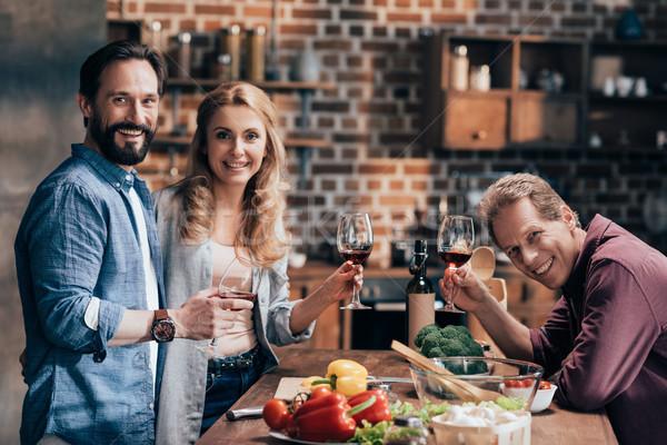 Freunde trinken Wein Kochen Abendessen heiter Stock foto © LightFieldStudios