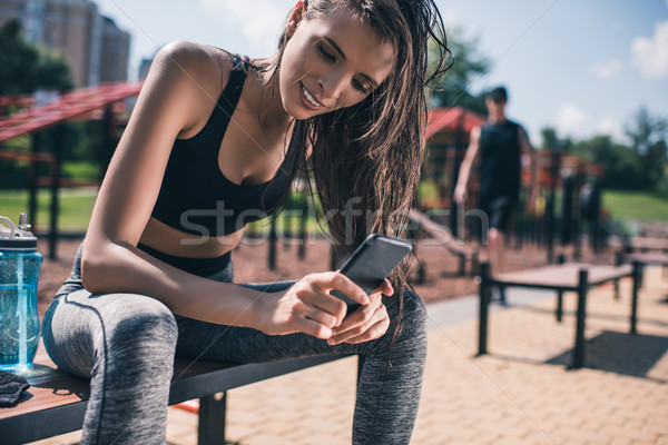 Stock photo: sportive woman using smartphone