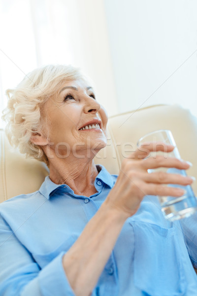 Vidrio agua sesión sillón sonriendo Foto stock © LightFieldStudios