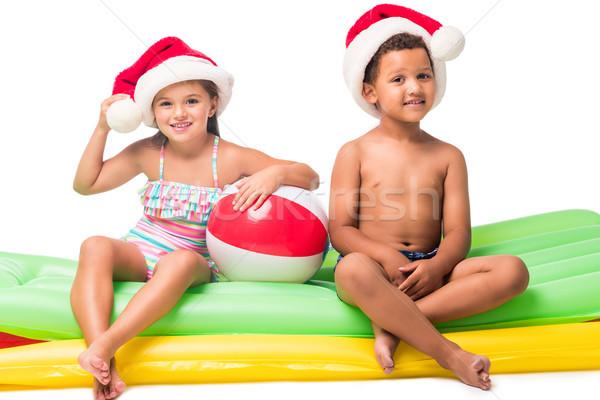 kids in santa hats on swimming mattresses Stock photo © LightFieldStudios