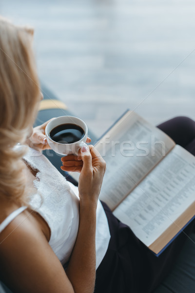 woman reading book and drinking coffee  Stock photo © LightFieldStudios