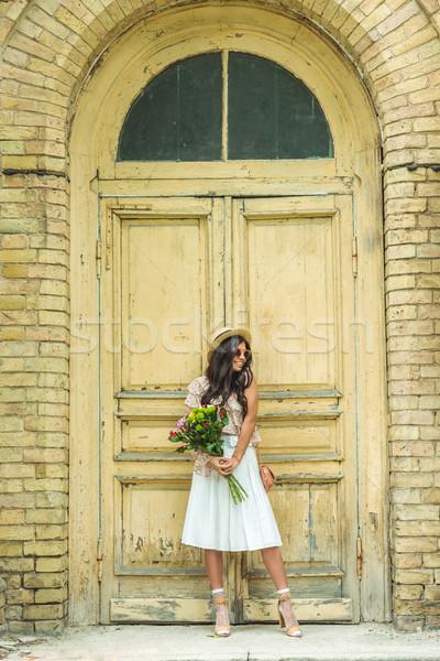 Gyönyörű lány virágcsokor virágok gyönyörű fiatal nő kalap Stock fotó © LightFieldStudios