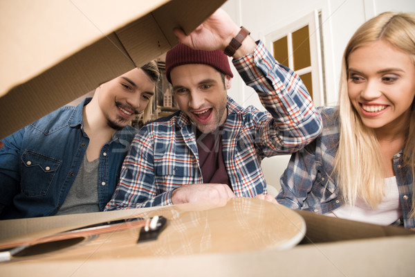 Close-up view of excited young friends opening box with guitar Stock photo © LightFieldStudios