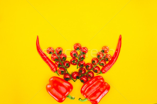 top view of fresh red peppers and cherry tomatoes isolated on yellow  Stock photo © LightFieldStudios
