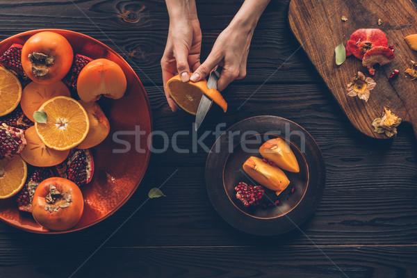 cropped image of woman peeling orange Stock photo © LightFieldStudios