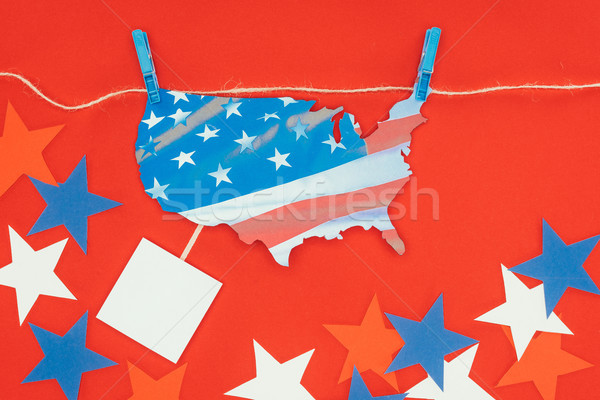 top view of piece of map with american flag hanging on rope and stars isolated on red Stock photo © LightFieldStudios