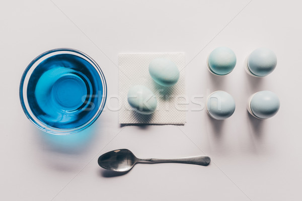 top view of glass with blue paint and chicken eggs on stands and napkin, easter concept Stock photo © LightFieldStudios