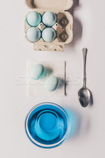 top view of glass with blue paint and chicken eggs in tray, easter concept Stock photo © LightFieldStudios