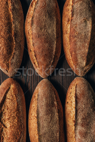close up view of arranged loafs of bread on wooden surface Stock photo © LightFieldStudios