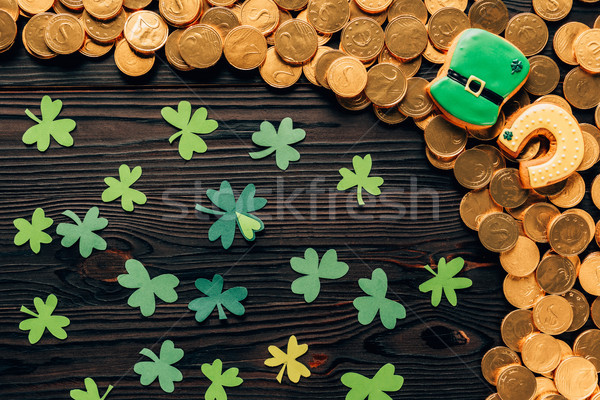 top view of paper shamrock and golden coins on wooden table, st patricks day concept Stock photo © LightFieldStudios
