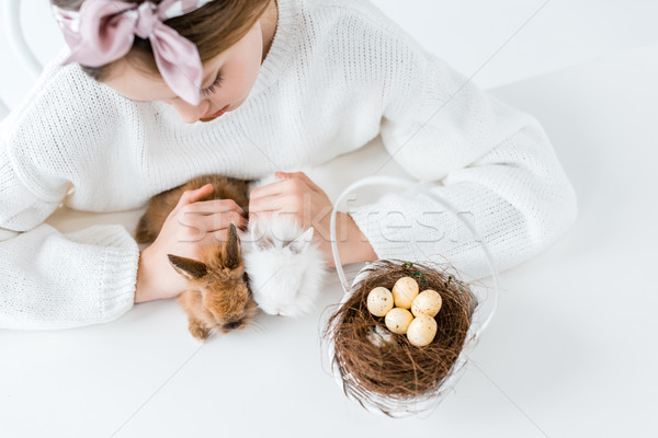 cropped shot of girl looking at cute furry rabbits and basket with easter eggs in nest  Stock photo © LightFieldStudios
