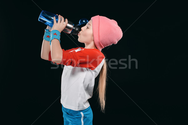 girl in sportswear drinking from sport bottle isolated on black. athletics children concept Stock photo © LightFieldStudios