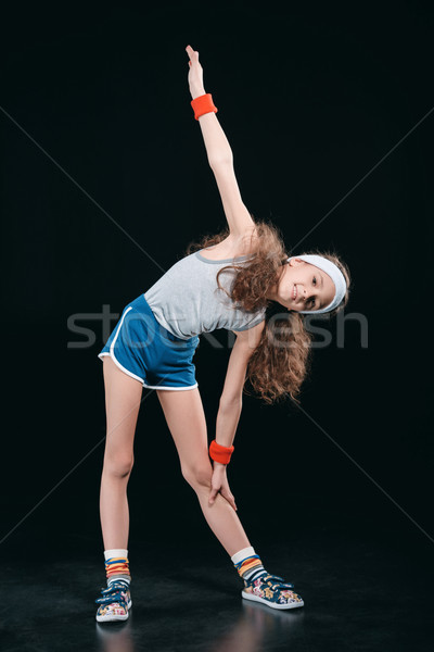 Stock photo: girl in sportswear exercising isolated on black. acting kids, 12 year old kids concept