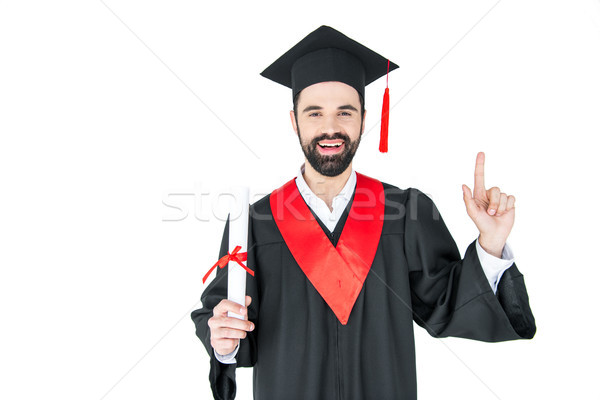 Happy young student holding diploma and pointing up with finger Stock photo © LightFieldStudios