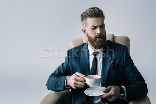 portrait of elegant businessman holding cup of coffee on grey Stock photo © LightFieldStudios