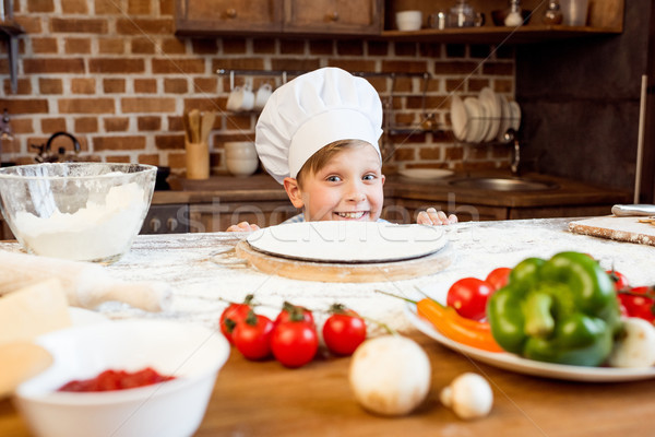 little boy making pizza dough with pizza ingredients in kitchen Stock photo © LightFieldStudios