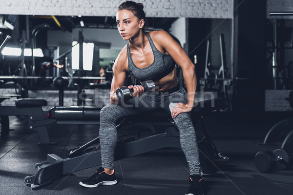 sportive woman exercising with dumbbell Stock photo © LightFieldStudios
