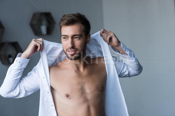 man putting on shirt Stock photo © LightFieldStudios
