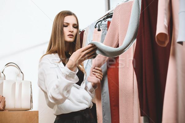 Butik vonzó divatos lány választ ruházat Stock fotó © LightFieldStudios