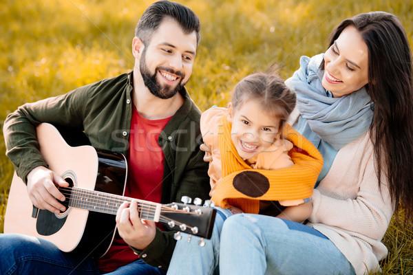 man playing guitar with family Stock photo © LightFieldStudios