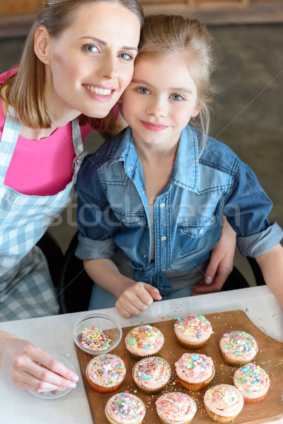 high angle view of smiling mother and daughter with cupcakes on board Stock photo © LightFieldStudios