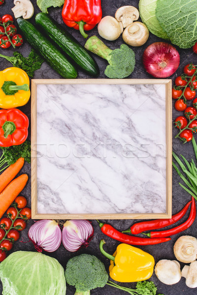 top view of fresh raw vegetables and blank marble board on black Stock photo © LightFieldStudios