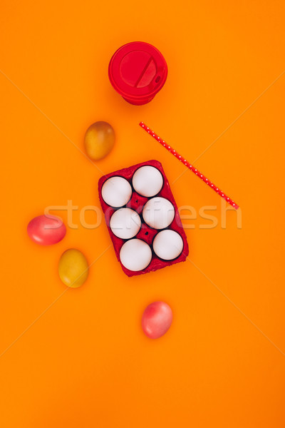 top view of chicken eggs in red egg tray and coffee isolated on orange Stock photo © LightFieldStudios