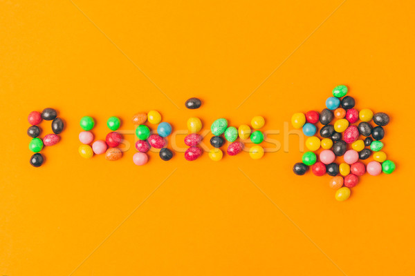 top view of purim lettering made of candies and star isolated on orange Stock photo © LightFieldStudios