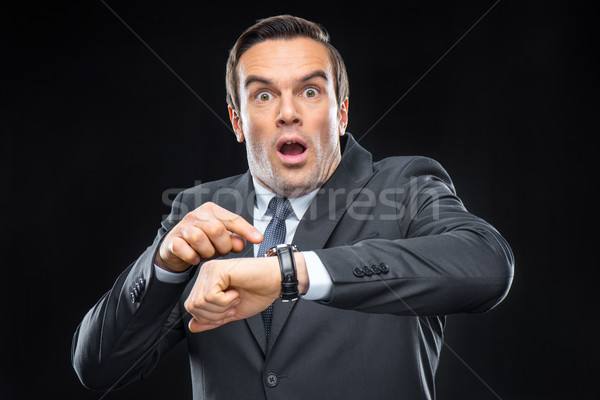Scared businessman with wristwatch Stock photo © LightFieldStudios