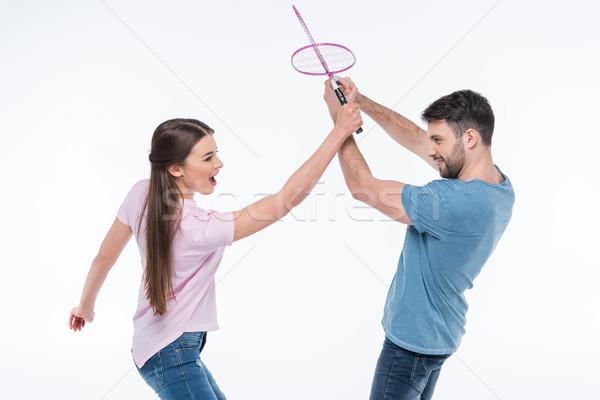 portrait of couple fighting with badminton rackets on white Stock photo © LightFieldStudios
