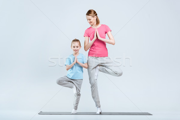 Smiling sporty mother and daughter practicing yoga together, Vrikshasana yoga pose or tree pose on w Stock photo © LightFieldStudios