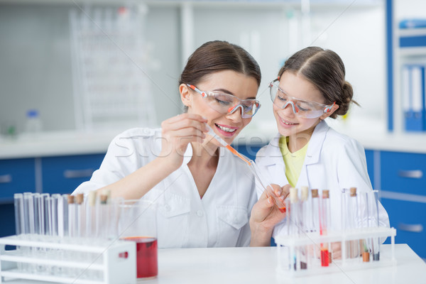 portrait of smiling girl student watching scientist teacher making experiment in lab Stock photo © LightFieldStudios