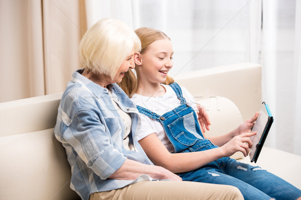Smiling grandmother and granddaughter sitting on sofa with digital tablet  Stock photo © LightFieldStudios