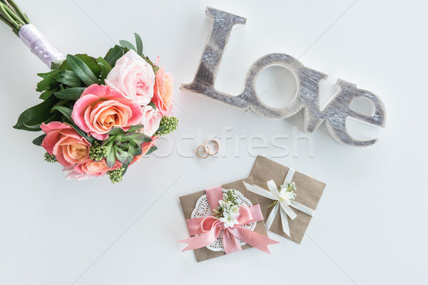 Stock photo: Top view of golden wedding rings, decorative envelopes, beautiful bouquet and love symbol, wedding i