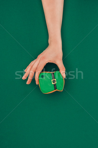 Stock photo: cropped image of woman holding cookie in shape of hat isolated on green, st patricks day concept