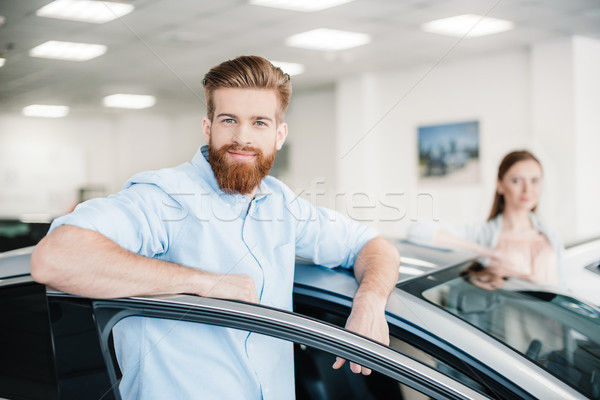 Happy couple standing at car in dealership salon, man looking at camera Stock photo © LightFieldStudios
