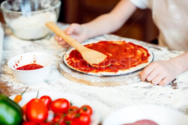 partial view of girl putting tomato sauce on pizza dough Stock photo © LightFieldStudios