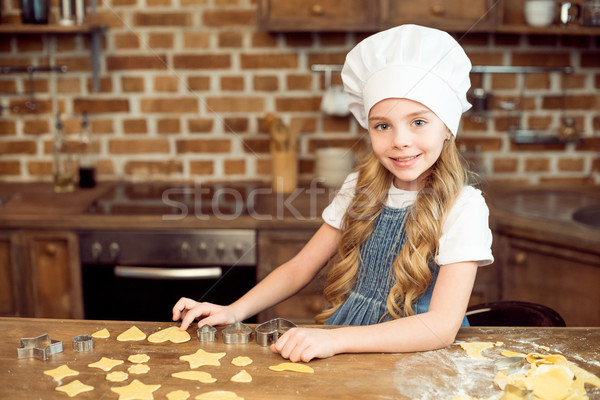 portrait of little girl in chef hat making shaped cookies in kitchen Stock photo © LightFieldStudios