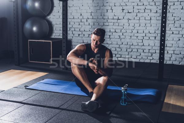 sportive man looking at smartwatch Stock photo © LightFieldStudios