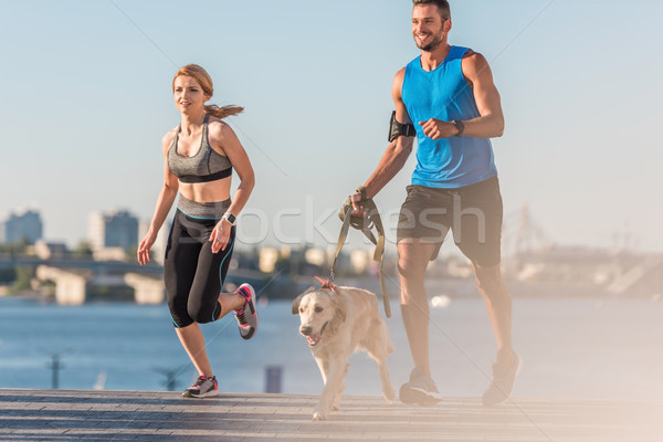 sportswoman and sportsman jogging with dog Stock photo © LightFieldStudios