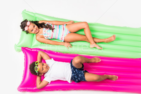 kids in swimwear on swimming mattresses  Stock photo © LightFieldStudios